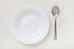 Top view of white deep plate and spoon on plaster Stock Photos