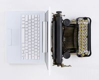 Top view of a white desk with old fashioned typewriter back-to-back with a laptop computer. Top view of a white desk with old fashioned typewriter back-to-back royalty free stock photos