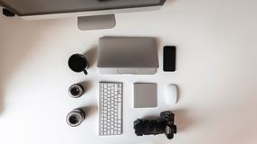 Top view of the white desktop, which has a laptop, lenses for the camera, a modern professional camera, a black cup of coffee. Keyboard and telephone. Modern royalty free stock image