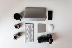 Top view of the white desktop, which has a laptop, lenses for the camera, a modern professional camera, a cup of coffee, keyboard. And telephone. Modern stock image