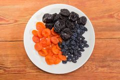 Some traditional dried fruits on dish on old rustic table. Top view of the white dish with dark-colored raisins, dried plums and dried apricots on an old wooden Stock Images