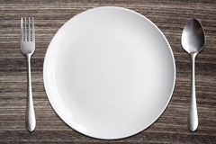 Top view White dish spoon fork on wood background Stock Photos