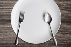 Top view White dish spoon fork on wood background Royalty Free Stock Images