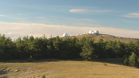 Top view of white dome of observatory at top of hill. Shot. Panoramic view of astronomical observatory complex in wild. Against blue sky with clouds. Concept of stock video