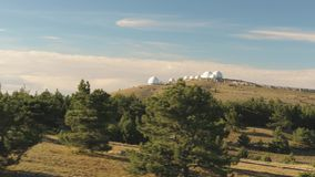 Top view of white dome of observatory at top of hill. Shot. Panoramic view of astronomical observatory complex in wild stock footage