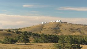 Top view of white dome of observatory at top of hill. Shot. Panoramic view of astronomical observatory complex in wild. Against blue sky with clouds. Concept of stock footage