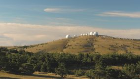 Top view of white domed buildings of observatories on hill. Shot. Astronomical research facilities and large. Observatories located at top with beautiful sunset stock video footage