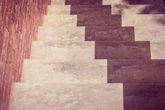 Top View Of White Empty Stairs Beside Brown Brick Wall With Shadow Fall On The Floor