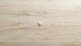 White heart made of stone lying on a woodenk desk Stock Image