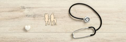 White heart with medical stethoscope next to a family. Top view of a white heart with medical stethoscope next to a family with three children royalty free stock image