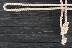 Top view of white nautical rope with knots on dark. Wooden tabletop royalty free stock photography