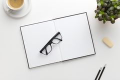 Top view of white office desk with notebook and supplies Stock Photos