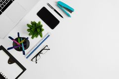 Top view of white office desk with office supplies. Office supplies on white office desk. Minimal simplicity flat lay with copy space Royalty Free Stock Images