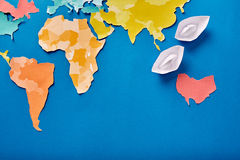 Top view of the white paper boats and international map while cut out of the colored paper on the blue background. Royalty Free Stock Photography