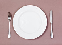 Top view of white plate, fork, knife on brown Stock Photo