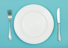 Top view of white plate, fork, knife on green Stock Photos