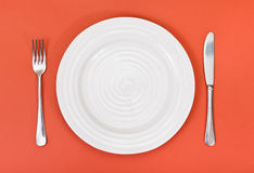 Top view of white plate, fork, knife on red Royalty Free Stock Photography