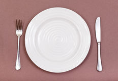 Top view of white plate, fork, knife set on brown Royalty Free Stock Image