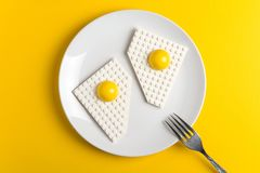 Top view of white plate with fried eggs of children`s designer on yellow paper background. Good morning concept. Top view. Flat lay royalty free stock images