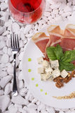 Top view of a white plate full of balyk, cheese and basil and a wineglass. Delicatessen on white stones. Royalty Free Stock Photo