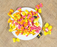 Top view of a white plate full of colorful Italian ravioli pasta on a canvas Stock Photography