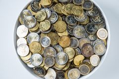 Top of view white plate full of euro coins.  royalty free stock image