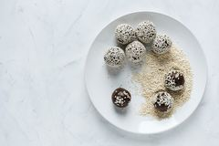 Energy ball on plate in sesame seeds. Top view of white plate with preparing energy ball in sesame seeds stock photography