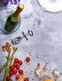 Close-up of a gray table with plate, champagne, tomatoes, asparagus, glasses, corkscrew, flowers on a gray background. Royalty Free Stock Image