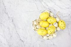 Top view of a white plate with yellow and imitated specks quail eggs on the marble background stock photography