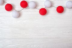 White and red cotton balls garland on a wooden background.Top view. Top view.White and red cotton balls garland on a wooden background stock photography