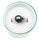 Top view of white ring with black pearl in box. Top view of white gold ring with black pearl in green box isolated on white background Stock Images