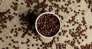 Bowl of coffee beans on canvas. Top view of white round bowl with coffee beans on rough canvas fabric with beans in mess around stock video footage