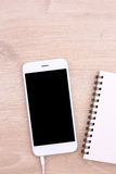 Top view white smartphone mockup with earphone and note paper on woode Stock Photography