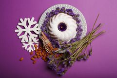 Top view of a plate with a ring cake, a candle, almond, cinnamon, snowflakes, twigs of flowers on a violet background. Top view of white snowflakes, almond Stock Image