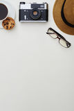 Top view of white surface with hat, eyeglasses, camera and a cup. Top view of white surface with hat, eyeglasses, photo camera and a cup of coffee with cookie Royalty Free Stock Images