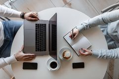 Top view on a white table at which sits a business man with a laptop and a female freelancer with a notepad with a mobile phone. Top view on a white table at stock image