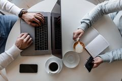 Top view on a white table at which sits a man with a laptop and a woman with a notepad with a mobile phone with a cup of coffee. Top view on a white table at stock photo