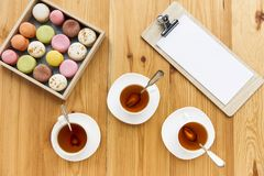 Top view of white tea cups, tasty macarons in box and blank paper sheet. On clipboard royalty free stock images
