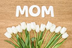 Top view of white tulips and word mom on wooden table, mothers day concept royalty free stock photography