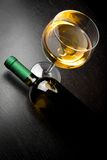 Top of view of white wine glass near bottle. On old wood table Stock Images