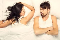 Top view.White young girl sleeping in bed. White bearded men looks at her. Couple in bed Royalty Free Stock Image