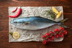 Fresh tuna with tomatoes, oil and spices. Top view of whole fresh tuna fish with tomatoes, lemon and spices on wooden background Stock Image