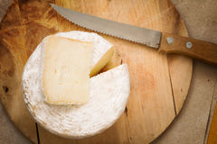 Top view of whole mature cheese on chopping board Stock Images