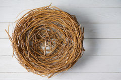 Top view of wicker nest over white wooden planks Royalty Free Stock Photography