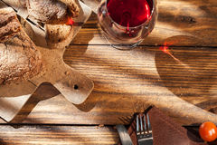 Top view of wine and bread on served wooden table. Top view of wine and bread on wooden table with fork and knife Royalty Free Stock Photography