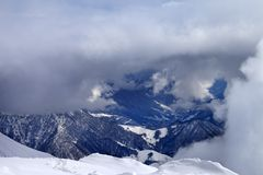 Top view on winter snowy mountains in clouds Royalty Free Stock Photos