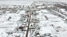 Top view of a winter village. The rural settlement is covered with snow. Snow and winter in the village.  stock footage