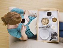 Top View of a Woman and Breakfast Tray. A woman sitting with a breakfast tray on her lap.  She is drinking coffee. Horizontally framed shot Stock Image