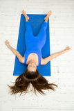 Top view of a woman in Corpse pose, white studio. Top view of a young attractive woman practicing yoga, lying in Dead Body, Corpse exercise, Savasana pose Royalty Free Stock Images