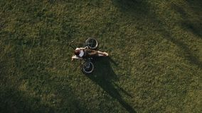 Top view woman cyclist lying on green grass in city park and using mobile phone. Young woman resting on grass in city park on background bike lying on lawn stock video footage